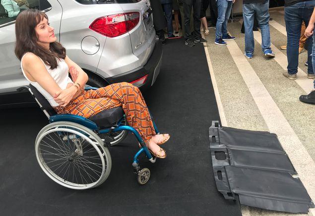 A estilista Michele Simões com o tapete portátil feito pela Ford, que pode ser usado por cadeirantes para superar desníveis de calçada